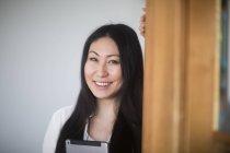 Asiatische Frau an die Tür gelehnt und hält digital-Tablette — Stockfoto
