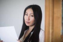 Employé de bureau asiatique tenant des papiers dans la porte — Photo de stock