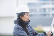 Female engineer in white hard hat holding blueprint — Stock Photo