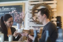 Young woman passing cup of coffee to boyfriend in cafe — Stock Photo