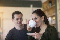 Donna che beve il caffè con il ragazzo e che osserva via — Foto stock