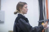 Weibliche Fabrikarbeiter aufschreiben Test Lesungen in Zwischenablage — Stockfoto