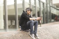 Young man sitting on street and using digital tablet — Stock Photo