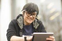 Азиатские человек с оголовьем и очки с помощью цифрового планшета на улице — стоковое фото