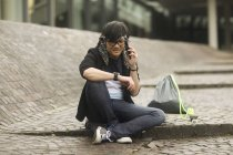 Young man talking on phone and looking down at wristwatch — Stock Photo