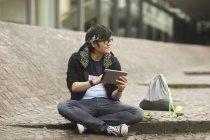 Молодой человек Холдинг цифрового планшета и глядя на улице — стоковое фото