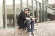 Young man with headband using digital tablet on street — Stock Photo