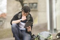 Young man with hand on chin using digital tablet on street — Stock Photo