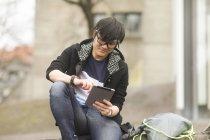 Jeune homme avec bandeau à l'aide de tablette numérique sur rue — Photo de stock