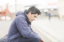 Homem adulto médio no casaco sentado na calçada — Fotografia de Stock
