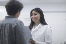 Female doctor talking to patient in clinic — Stock Photo