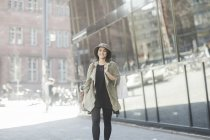 Young woman in trench coat walking with shopping bag in city — Stock Photo