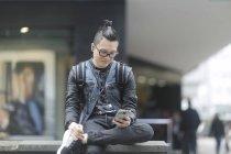 Homem com fones de ouvido usando smartphone na cidade — Fotografia de Stock
