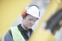 Engineer in protective headphones examining equipment on construction site — Stock Photo