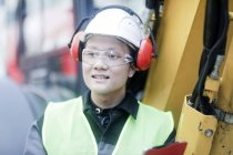 Male engineer in protective headphones working on construction site — Stock Photo