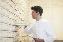 Farmacêutico masculino com tablet digital olhando na gaveta da farmácia — Fotografia de Stock