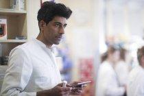Droghiere adulto metà tenendo del medicamento e utilizzando la tavoletta digitale in farmacia — Foto stock