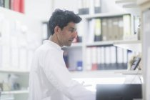 Mid adult pharmacist working in drugstore, side view — Stock Photo