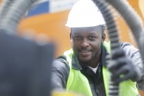 Construction worker looking in camera while holding tubes on building site — Stock Photo