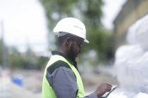Side view of African American engineer using digital tablet on construction site — Stock Photo