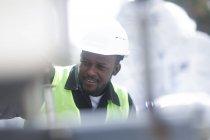 Construction worker using digital tablet for adjusting equipment — Stock Photo