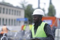 African American engineer holding digital tablet at building site — Stock Photo