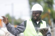 Mid adult engineer holding digital tablet and gesturing on building site — Stock Photo
