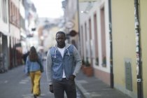 Seguros mediados hombre adulto en denim jacket de pie en la calle en la ciudad - foto de stock