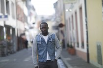 Confident mid adult man in denim jacket standing on street in town — Stock Photo