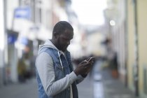 Mid adult man using smartphone on street — Stock Photo