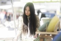 Young woman choosing crockery at marketplace in town. — Stock Photo