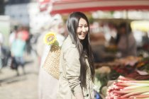 Young woman choosing stalks of rhubarb at marketplace in town. — Stock Photo