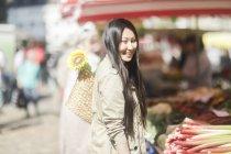Mujer joven elegir tallos de ruibarbo en el mercado de la ciudad - foto de stock