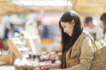 Young woman buying strawberries at marketplace in town. — Stock Photo