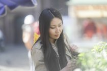 Asian woman choosing greens at marketplace in town. — Stock Photo