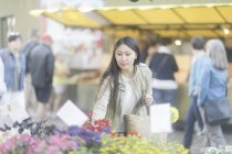 Asian woman choosing red flowers at market in town. — Stock Photo