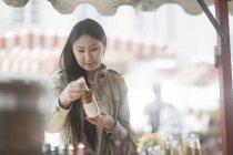 Frau mit Flasche Flüssigkeit auf dem Marktplatz in der Stadt — Stockfoto
