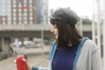 Young woman holding red portable speaker in city. — Stock Photo