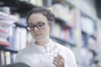 Feminino químico com tablet digital modelo molecular no laboratório de análise — Fotografia de Stock