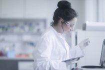 Female scientist with digital tablet putting microtube in centrifuge in laboratory. — Stock Photo