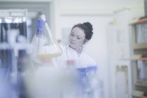 Female technician with digital tablet examining large flask with liquid in laboratory. — Stock Photo