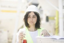 Portrait of building surveyor standing with papers and takeaway coffee in hands at construction site — Stock Photo