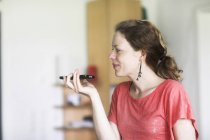 Side view of woman holding smartphone and using speakerphone in home interior. — Stockfoto