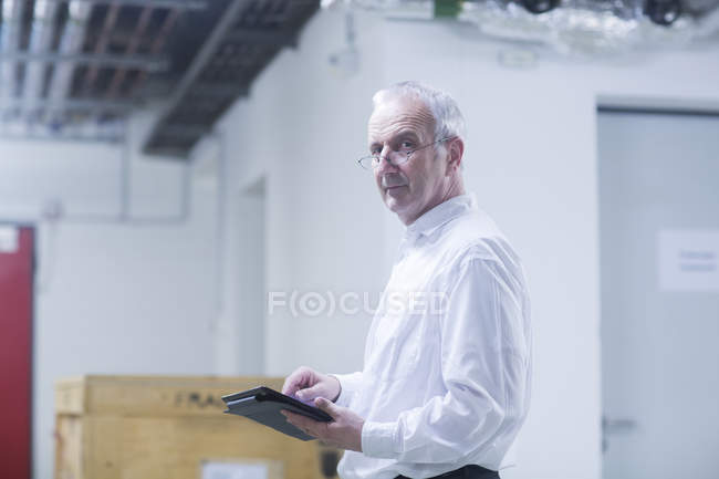 Engineer with tablet at production plant — Stock Photo