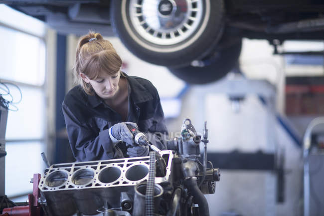Woman mechanic repairing engine — Stock Photo