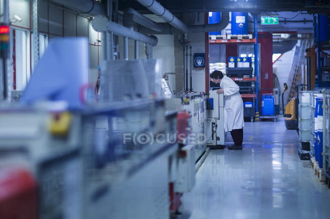 Woman checking equipment at industrial plant — Stock Photo