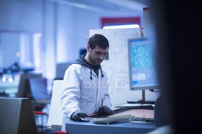 Людина в лабораторію пальто на робочому місці — стокове фото