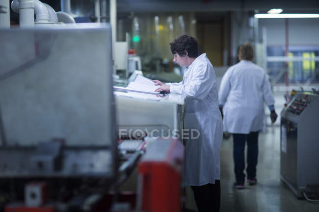 Woman in lab coat reading papers — Stock Photo