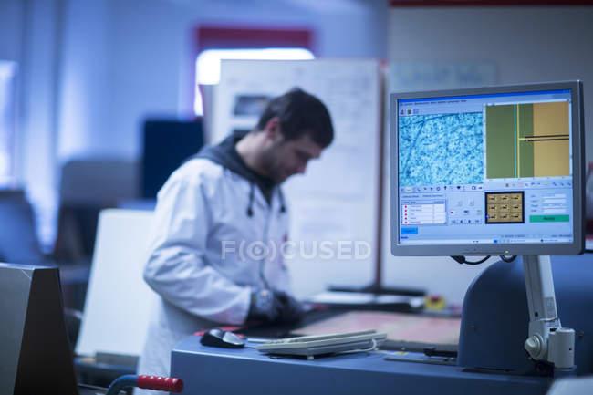 Mann im Laborkittel am Arbeitsplatz — Stockfoto