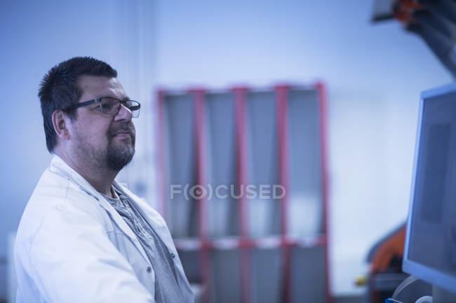 Homme en blouse de laboratoire sur le lieu de travail — Photo de stock